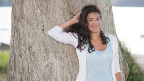 Gladlynt ung kvinna som ler med en hand bak huvudet Royaltyfri Foto