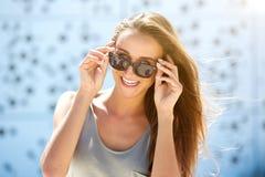 Gladlynt ung kvinna som ler med solglasögon Arkivbild