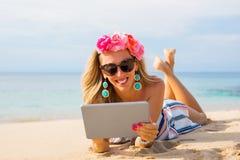 Gladlynt ung kvinna som ligger på stranden i sand och använder minnestavlan fotografering för bildbyråer