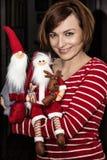 Gladlynt ung kvinna som poserar med två santas, julplats Royaltyfri Foto