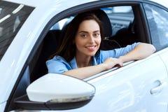Gladlynt ung kvinna som sitter i en bil royaltyfri foto