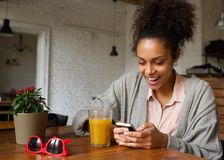 Gladlynt ung kvinna som skriver ett textmeddelande på mobiltelefonen arkivbilder
