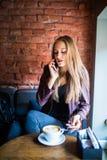 Gladlynt ung kvinna som talar på telefonen och ler, medan tycka om kaffe i kafé Royaltyfri Fotografi