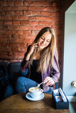 Gladlynt ung kvinna som talar på telefonen och ler, medan tycka om kaffe i kafé Royaltyfri Bild