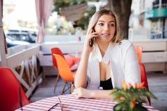 Gladlynt ung kvinna som talar på telefonen och ler, medan tycka om kaffe i kafé Arkivbilder