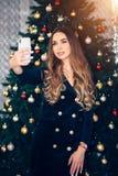 Gladlynt ung kvinna som tar en julselfie med smartphonen nära julträd royaltyfri fotografi