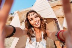 Gladlynt ung kvinna som tar selfie på stranden Royaltyfria Bilder