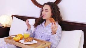 Gladlynt ung kvinna som tycker om frukosten arkivfilmer