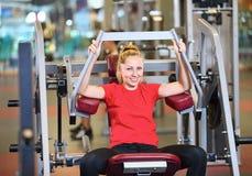 Gladlynt ung kvinna som ut fungerar i idrottshall Royaltyfri Bild