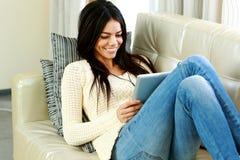 Gladlynt ung kvinna som vilar på en soffa med minnestavladatoren arkivbilder