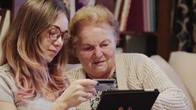 Gladlynt ung kvinna som visar hennes farmor hur man använder en minnestavla stock video