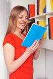 Kvinnaläsning boka och le Arkivbilder