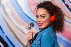 Gladlynt ung kvinnlig hållande audiocassette Arkivbild