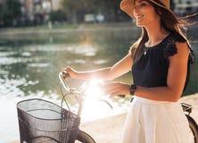 Gladlynt ung kvinnlig på parkera med hennes cykel arkivfoton