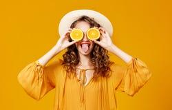 Gladlynt ung lockig kvinnaflicka med apelsinen p? gul bakgrund arkivbild