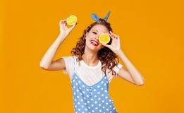 Gladlynt ung lockig kvinnaflicka med apelsinen p? gul bakgrund royaltyfri fotografi