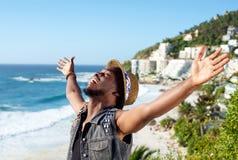 Gladlynt ung man med armspridning som är öppen på stranden arkivbilder