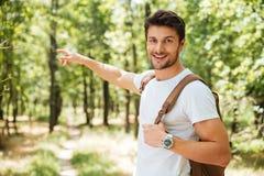 Gladlynt ung man med ryggsäcken som pekar bort i skog arkivbild