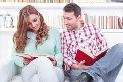 Gladlynt ung man och kvinna som tillsammans läser olik wh för böcker royaltyfri fotografi