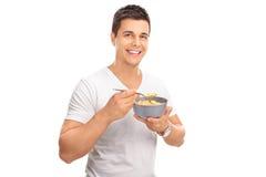 Gladlynt ung man som äter sädesslag från en bunke Royaltyfria Foton