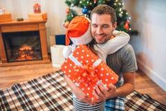 Gladlynt ung man som embrcing hans barn och och att le Han rymmer pesent som fick från dotter Hon bär den röda hatten dem royaltyfri bild