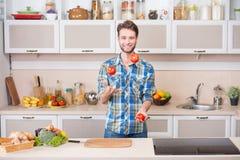 Gladlynt ung man som jonglerar tomater medan Arkivfoton