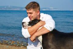 Gladlynt ung man som ler och kramar hans hund på stranden royaltyfria bilder