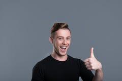 Gladlynt ung man som ler och lyfter tummen fotografering för bildbyråer