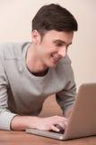 Gladlynt ung man som ligger på golv med bärbara datorn Royaltyfri Bild