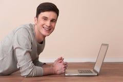 Gladlynt ung man som ligger på golv med bärbara datorn fotografering för bildbyråer