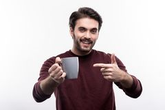 Gladlynt ung man som pekar på koppen kaffe arkivfoto