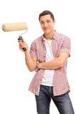 Gladlynt ung man som rymmer en målarfärgrulle royaltyfria foton