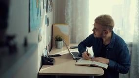 Gladlynt ung manlig student med exponeringsglas och gult hår som hemma arbetar Skrivbord Den kompetenta hem- freelanceren gör anm arkivfilmer