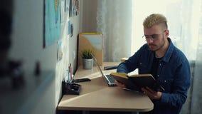 Gladlynt ung manlig student med exponeringsglas och gult hår som hemma arbetar Skrivbord Kompetent hem- freelancer att bläddra på lager videofilmer