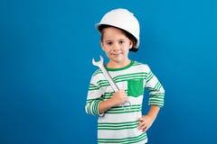 Gladlynt ung pojke i den skyddande hjälmen som poserar med skiftnyckeln fotografering för bildbyråer