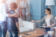 Gladlynt ung psykoterapeut som välkomnar nya patienter arkivfoton