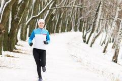 Gladlynt ung sportkvinna på utomhus- aktivitet för vinter fotografering för bildbyråer