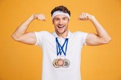 Gladlynt ung spotrsman med tre medaljer som visar biceps Royaltyfria Bilder