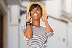 Gladlynt ung svart kvinna som talar på mobiltelefonen Royaltyfria Bilder