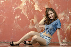 Gladlynt ung tonårig flicka i grov bomullstvillkortslutningar Royaltyfri Bild