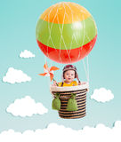 Gladlynt unge på ballongen för varm luft i himlen fotografering för bildbyråer