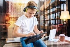 Gladlynt unge som spelar med hans nya minnestavla och lyssnar till musik royaltyfria foton