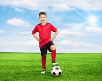 Gladlynt unge som står över en fotboll på fält royaltyfria bilder