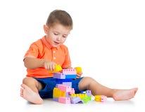 Gladlynt ungepojke som leker med konstruktionsuppsättning över vitbaksida Arkivfoto