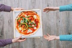 Gladlynt ungt bud som rymmer en pizzaask, medan isolerat på vit Royaltyfri Bild