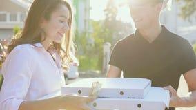 Gladlynt ungt bud som rymmer en pizzaask, medan isolerat på vit KurirDelivering Box With mat till klienten arkivfilmer