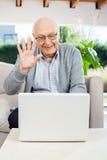 Gladlynt video för hög man som pratar på bärbara datorn arkivfoton