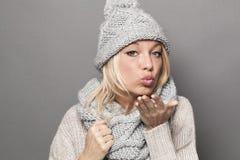 Gladlynt vinterkvinna som uttrycker mjukhet i att truta och kyssande tecken Arkivbild