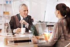 Gladlynt vuxen affärsman som talar med hans kvinnliga kollega arkivfoton