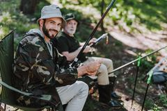 Gladlynt vuxen man som fiskar med hans pensionerade fader arkivbilder